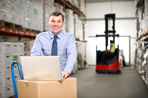 Image of businessman with laptop in warehouse